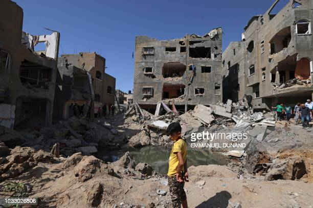 Palestinian child stands amidst the rubble of buildings, destroyed by Israeli strikes, in Beit Hanun in the northern Gaza Strip on May 21, 2021. - A...