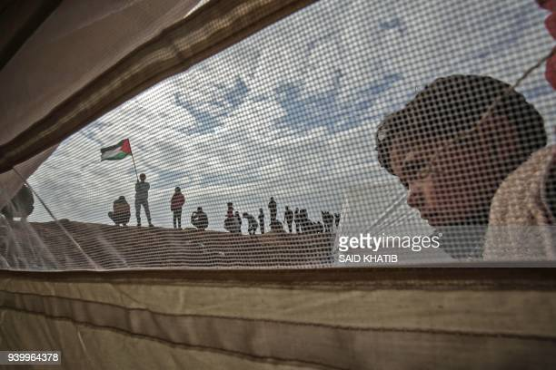 Palestinian child stands outside a tent during a a tent city protest near Khan Yunis in the southern Gaza Strip on March 30 2018 Land Day marks the...