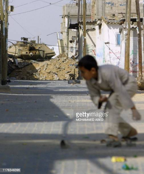 Palestinian child takes cover during an Israeli army incursion into the Rafah refugee camp in the southern Gaza Strip 15 April 2004. Twenty...