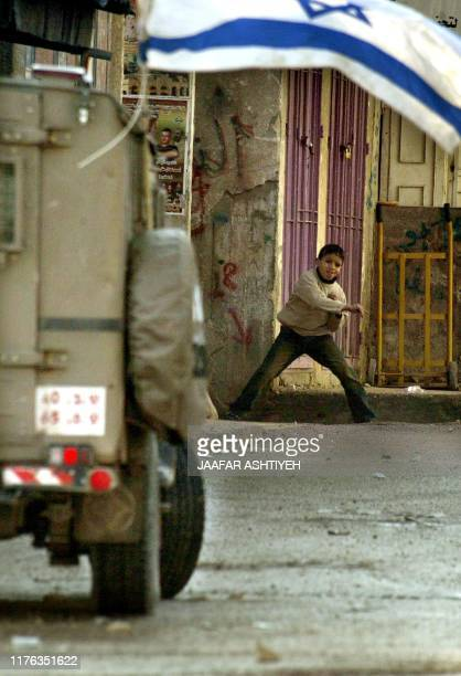A Palestinian child throws stones at an armoured Israeli jeep during clashes 16 January 2005 in Balata refugee camp near to the West Bank city of...