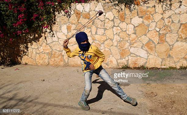 A Palestinian child throws stones at Israeli forces during clashes with Israeli soldiers over the Jewish settlement of Qadomem at Kofr Qadom village...