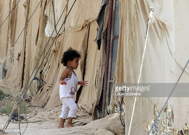 A Palestinian child walks into her family's tent during a visit by United Nations High Commissioner for Refugees Antonio Guterres on June 18 to a...