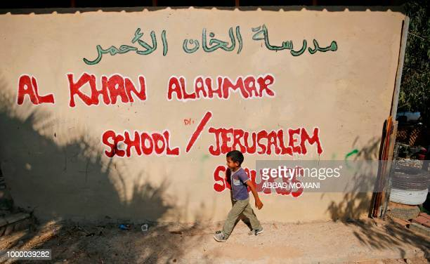 A Palestinian child walks past the wall of the Khan alAhmar school on the first day of classes in the Bedouin village in the occupied West Bank on...
