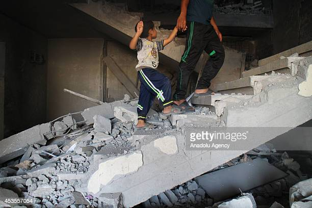 Palestinian child with his brother are seen inside debris of the buildings destroyed by Israeli army as Palestinians get back to Beit Lahia to...