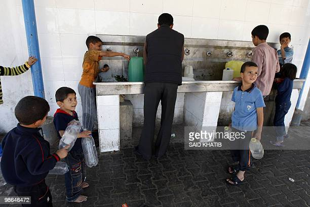 Palestinian children and men fill bottles and containers with water at the United Nations Relief and Works Agency headquarters in Khan Yunis refugee...