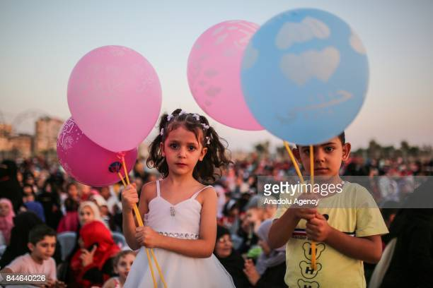 Palestinian children attend a wedding ceremony of 200 couples organised by Hamas as they hold balloons in Gaza City Gaza on September 08 2017...