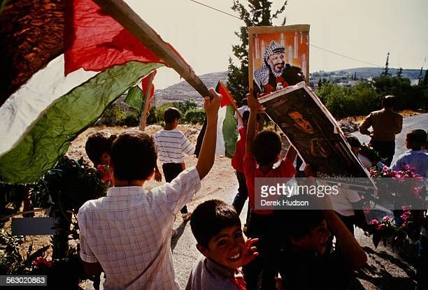 Palestinian children carry placards and Palestinian flags to show their support for Yasser Arafat during the intifada occupied Palestinian...