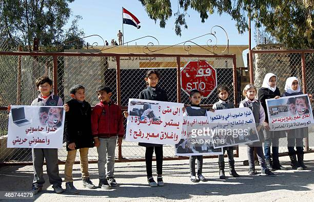 Palestinian children carry placards during a rally in front of the Rafah border crossing with Egypt in the southern Gaza Strip on January 29...