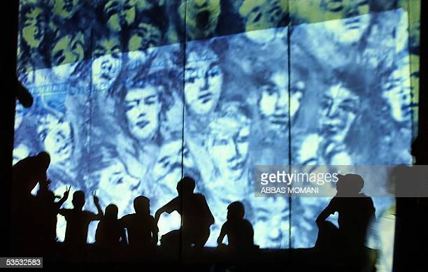 Palestinian children cast their shadows on the wall while watching a documentary film on the controversial Israeli separation barrier and the former...