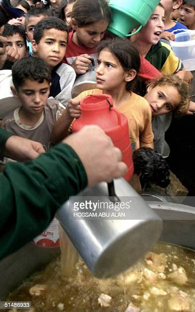Palestinian children crowed to be served with soup at a charity house in the West Bank town of Hebron 16 October 2004 on the second day of the holy...