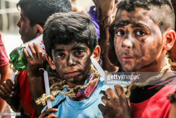 TOPSHOT Palestinian children demonstrate with candles at the Erez crossing with Israel near Beit Hanun in the northern Gaza Strip on July 24 2018...