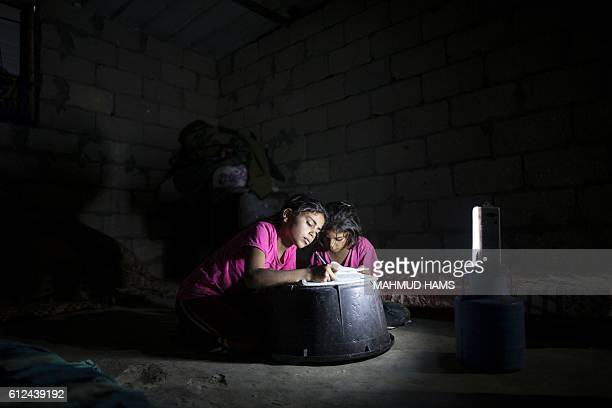 Palestinian children do their homework during a power cut in an impoverished area in the southern Gaza Strip city of Khan Yunis on October 4 2016 /...