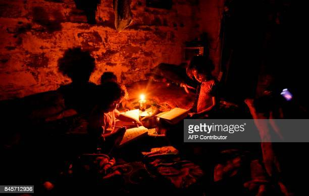 TOPSHOT Palestinian children do their homeworks during a power cut in an impoverished area in Gaza City on September 11 2017 Residents of Gaza home...