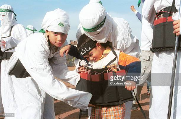 Palestinian children dressed as suicide bombers, put fake explosives on a small child December 9, 2001 after marching in commemoration of the 14th...