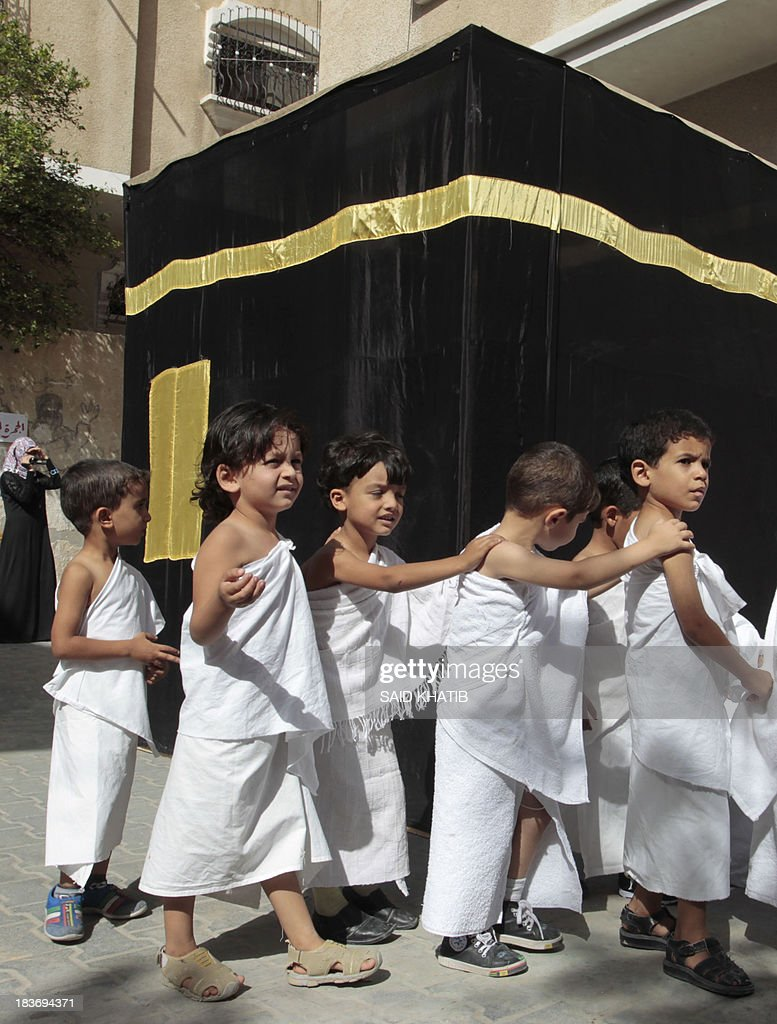 Palestinian children, dressed in Ihram, specials outfits worn during the Hajj pilgrimage, walk around a replica of the Kaaba stone which is found in the holy city of Mecca, Saudi Arabia, as youngsters learn about Islam and how to perform the rituals carried out during the annual Hajj, at their Kindergarten in Rafah town in the southern Gaza Strip, on October 9, 2013. Muslims from around the world will flood the holy city of Mecca this week to perform the annual Hajj pilgrimage, which is one of the five pillars of Islam.