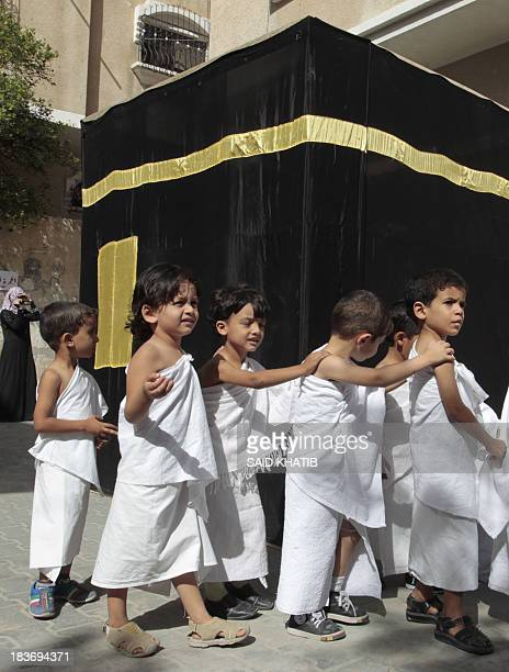 Palestinian children dressed in Ihram specials outfits worn during the Hajj pilgrimage walk around a replica of the Kaaba stone which is found in the...