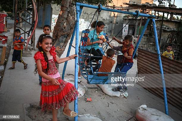 Palestinian children enjoy in Shujaiyyah neighborhood on July 18 in Gaza City at the Eid alFitr the threeday festival that follows the fasting month...