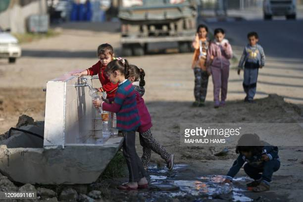 Palestinian children fill plastic bottles with water at a refugee camp in Khan Yunis in the southern Gaza Strip on April 11 2020 Only a few cases of...