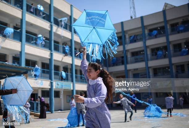 Palestinian children fly UNRWA logo printed kites outside their classrooms at a school belongs to United Nations Relief and Works Agency for...