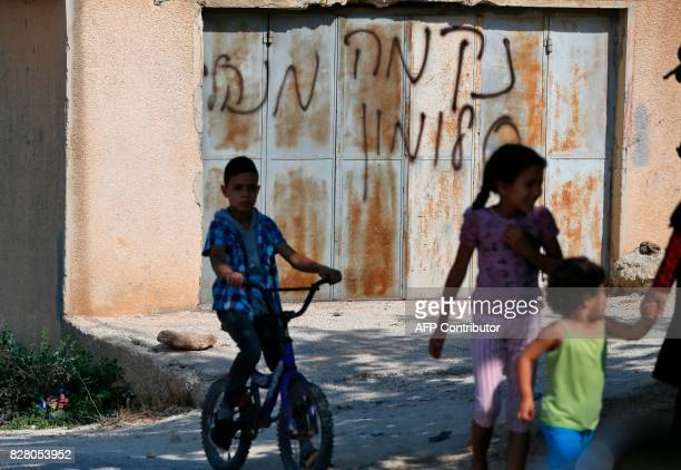 Palestinian children from the village of Umm Safa west of Ramallah in the occupied West Bank play near graffiti on the gate of a house reading in...