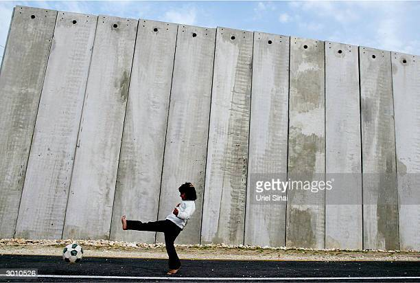 Palestinian children from the West Bank village of Masha play next to the controversial wall built by Israel around the West Bank and through Arab...