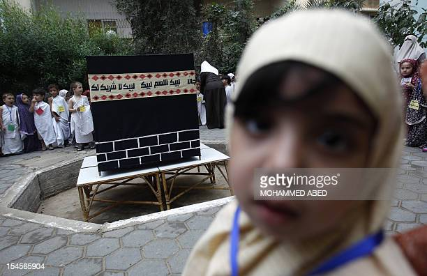 Palestinian children gather around a makeshift cube representing the holy Kaaba in Gaza City on October 22 as part of training children how to...