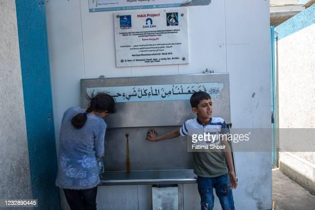 Palestinian children get water in an UNRWA school, after violent Israeli raids on the city of Beit Hanoun in northern Gaza on May 14, 2021 in Gaza...