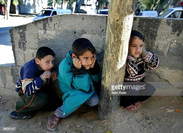 Palestinian children hide behind a wall during clashes between Israeli troops and Palestinian gunmen December 11, 2003 in the Rafah Refugee Camp,...