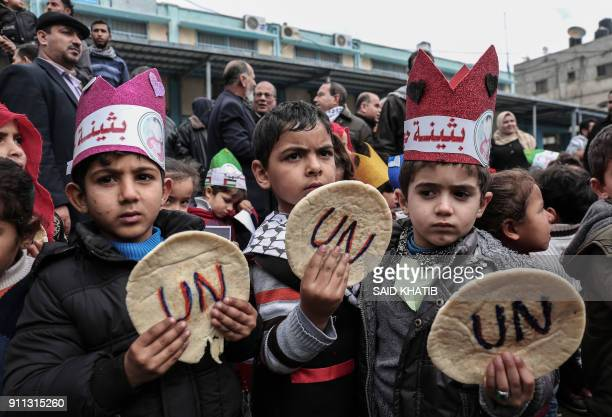 TOPSHOT Palestinian children hold bread patties during a protest against aid cuts outside the United Nations' offices in Khan Yunis in the southern...