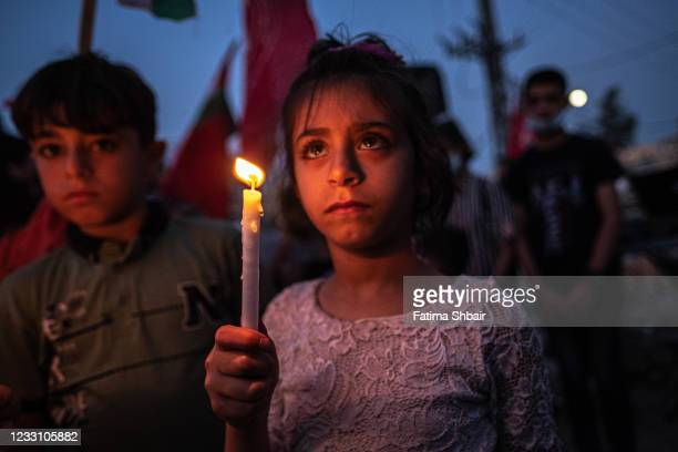 Palestinian children hold candles during a rally amid the ruins of houses allegedly destroyed by Israeli strikes, in Beit Lahia Northern Gaza Strip...