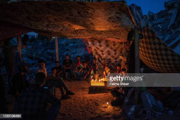 Palestinian children hold candles during a rally amid the ruins of houses destroyed by Israeli strikes, in Beit Lahia Northern Gaza Strip on May 25,...