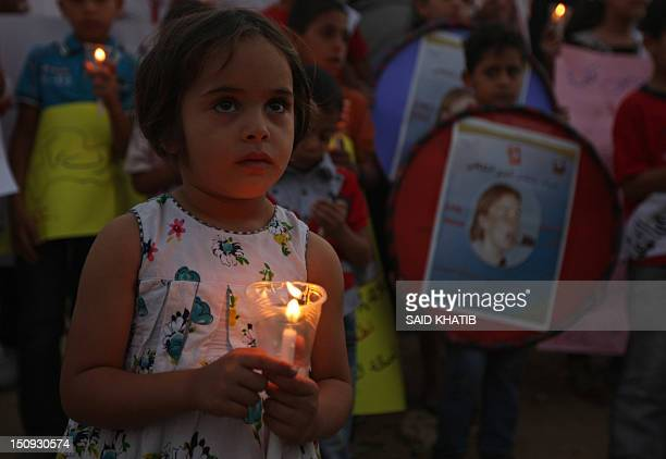 Palestinian children hold candles during a rally at a refugee camp in Rafah in the southern Gaza Strip on August 29 in solidarity with Rachael Corrie...