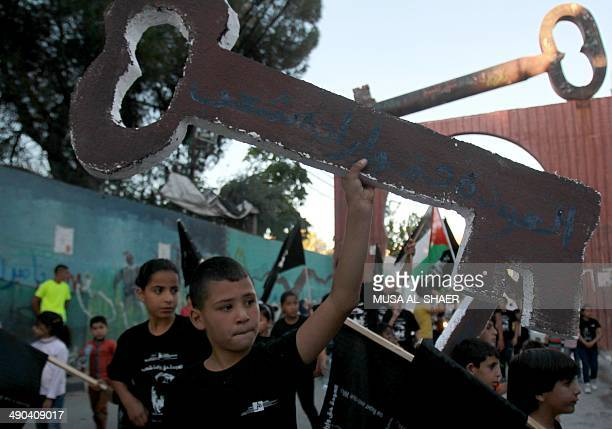 Palestinian children hold cutouts symbolizing a key as they take part in a commemoration on the eve of the 66th anniversary of the 'Nakba' at the...