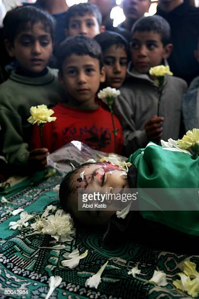 Palestinian children hold flowers as they stand next to the body of fivemonth old Mohammad Naser AlBuri as he lies at the mosque during his funeral...