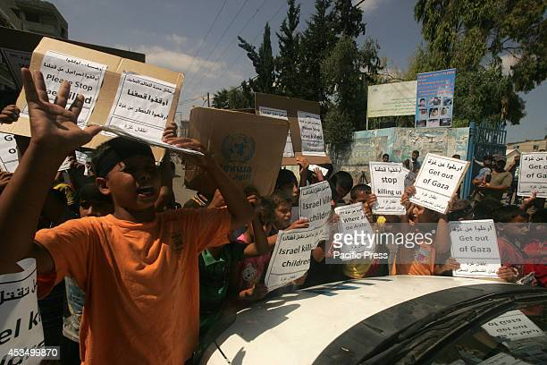 Palestinian children hold posters and banners outside an UNRWA school during a protest against the killing of children in Rafah in the southern Gaza...