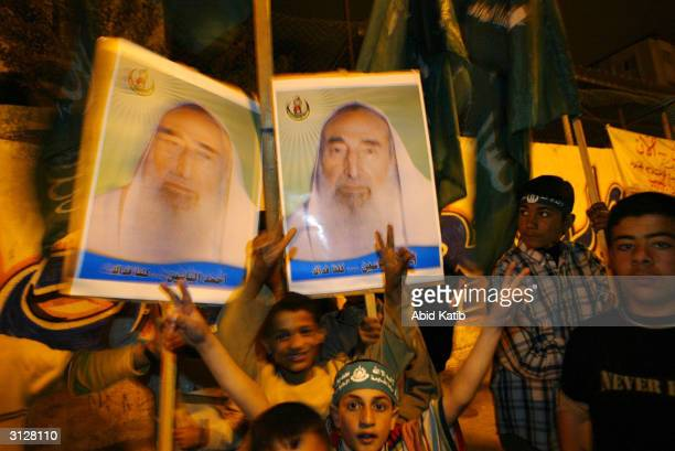 Palestinian children hold posters of assasinated Hamas leader Sheikh Ahmed Yassin as they participate in a night rally of the militant wing of Hamas...