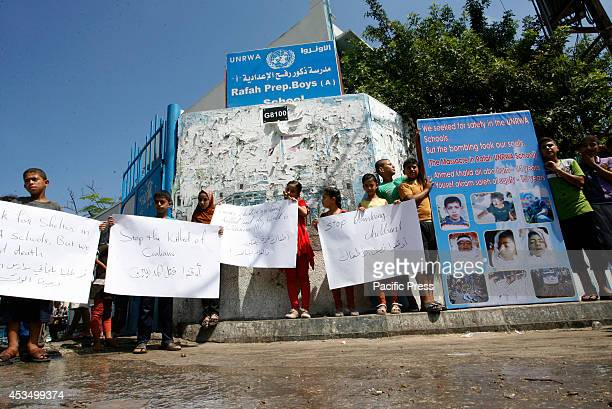 Palestinian children hold posters outside an UNRWA school during a protest against the killing of children in the southern city of Rafah a week after...