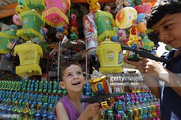 Palestinian children hold traditional Ramadan lanterns and fake guns in front of a market stall on June 27 2014 in Jabalia refugee camp northern of...