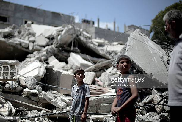 Palestinian children inspect wreckage of the alQassam mosque destroyed by Israeli airstrikes in Nuseirat Refugee Camp in Gaza on August 9 2014 Three...