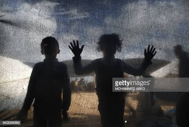 TOPSHOT Palestinian children look inside tents pitched by Palestinian on the Gaza border with Israel east of Jabalia on March 30 as Palestinian held...