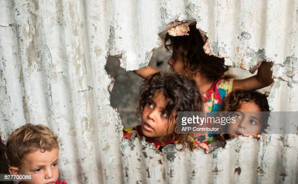 TOPSHOT Palestinian children look through a hole in a sheet metal fence outside their home in a poor neighbourhood in Gaza City on August 8 2017 /...