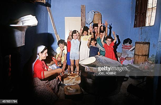 Palestinian children make the victory sign while a woman cooks bread in the refugee camp of Shatila near Beirut 23 June 1985 Des enfants palestiniens...