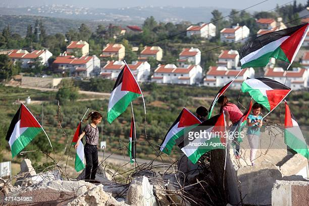 Palestinian children plant Palestinian flags on the debris of the demolished house in the village of Nabi Salih in Ramallah West Bank on April 28...
