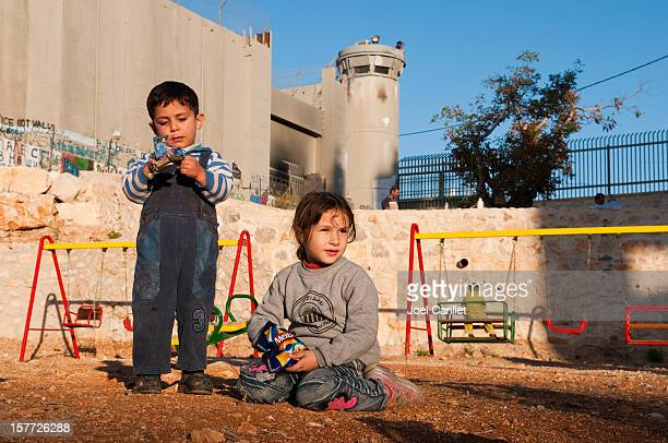 palestinian children at playground beside separation barrier wall in bethlehem - palestinian stock pictures, royalty-free photos & images