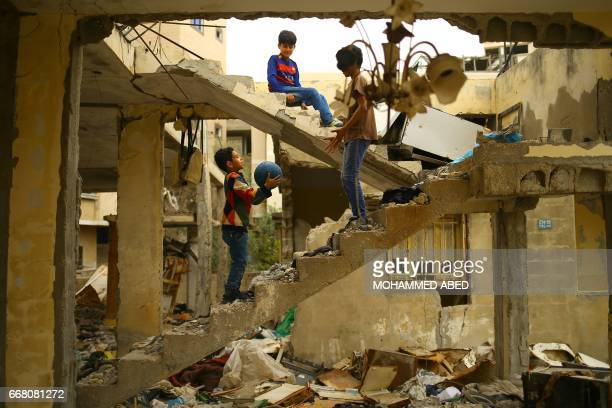 TOPSHOT Palestinian children play amidst the ruins of a building destroyed during the 50day war between Israel and Hamas militants during the summer...