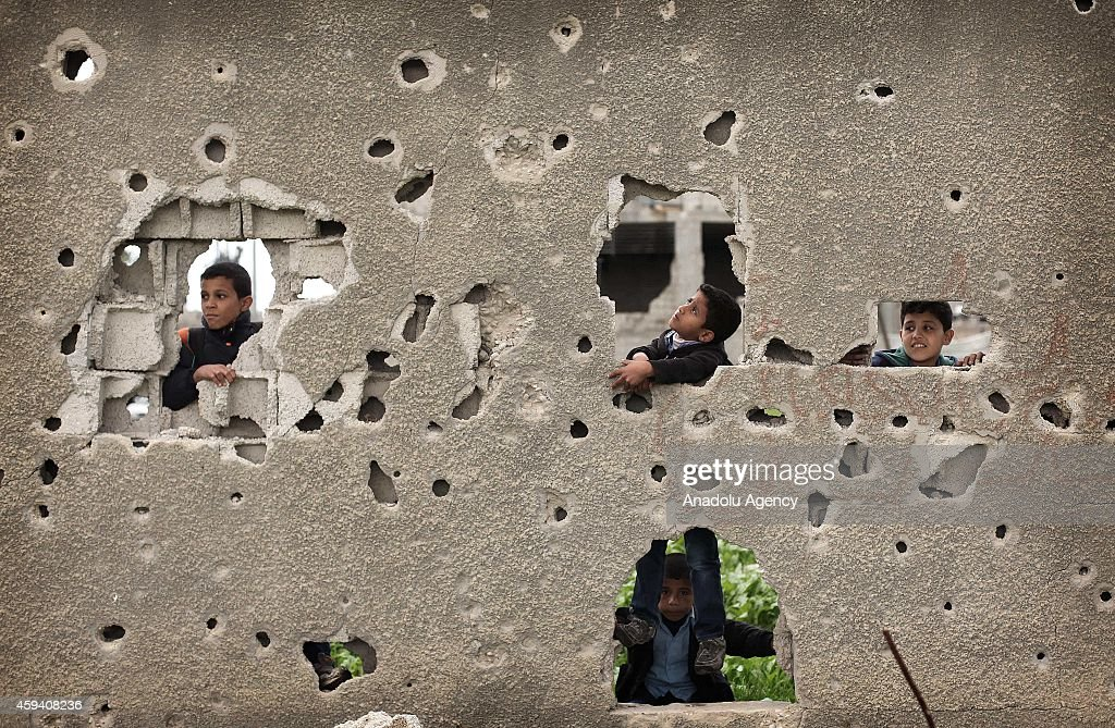 Palestinian children play around a damaged house in Gaza City, Gaza on November 22, 2014.