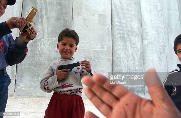 Palestinian children play by the separation wall in the village of A-tur located on the outskirts of East Jerusalem Tuesday March 01, 2005.