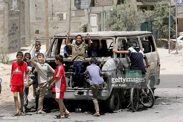 Palestinian children play in a burned vehicle belonging to Palestinian security men after it was set on fire by Hamas activists on July 19, 2005 in...