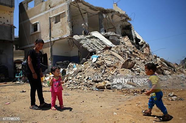Palestinian children play in front of the rubble of buildings which were destroyed during the 50-day war between Israel and Hamas militants in the...