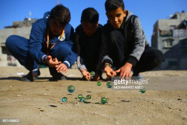 Palestinian children play marbles in a street in Gaza City on January 11 2017 / AFP / MOHAMMED ABED
